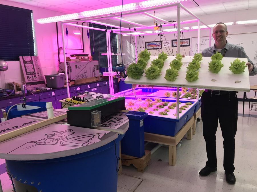 Mr. Tracy Bartels, a science teacher, stands amidst the aquaponics system in an extra science classroom at CHS.