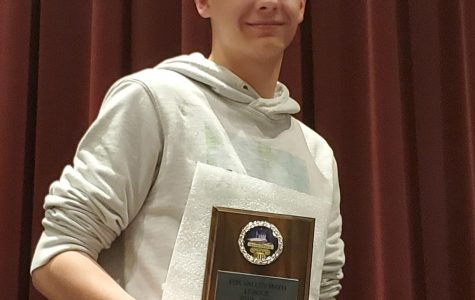 Senior James Austin accepts a plaque for being named First Team All-League in the Fox Valley Math League as one of the top eight scorers for the season across all grade- levels. It was the first time Austin won the award and was made possible by his score of 38 out of 40 points that night, March 9, during the last math meet of the season at Kimberly High School.