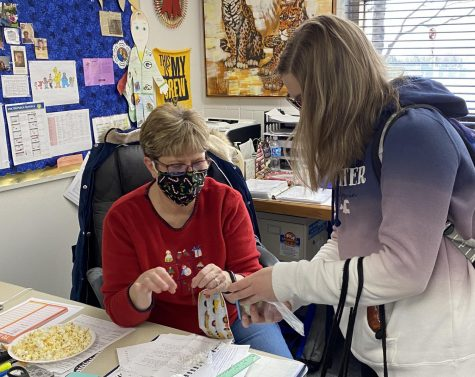 Mrs. Bonnie Mallmann has sewn over 2000 masks since the start of the pandemic. Here, she sits at her desk and adds toggles to the ear loops of a mask she gave to a student.