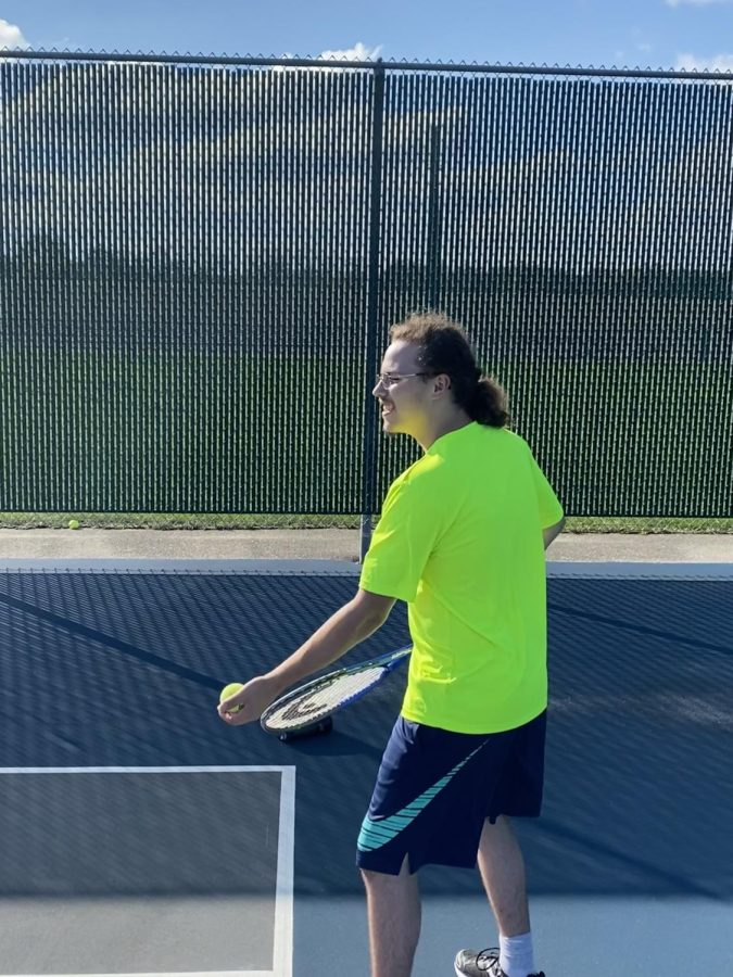 Photo by Alex Bowe  Senior Wyatt Yindra plays tennis after school with Mr. Tom Molitor and Mr. Scott Sabel, history teachers who are encouraging students to try tennis through a new co-curricular: Tennis Club.
